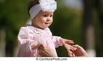 Close-up of the cute baby-girl playing and dancing in the...