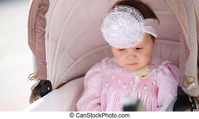 Close-up of the cute baby-girl sitting in the baby carriage....
