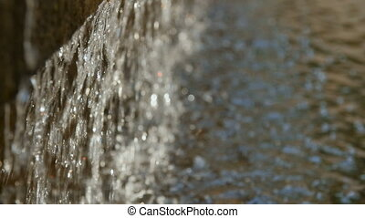 Close-up of the dripping water, in the sunlight. - Close-up,...