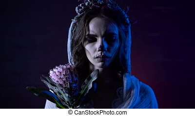 Close up of the face of a young lonely dead girl dressed in white wedding dress and veil with sad face and sewed mouth. Young woman with flower in her hand and halloween appearance is standing against horror background looking at the camera and closing her eyes. Horrifying woman dressed in white ...