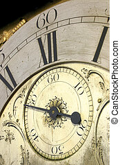 Close up of the face of an antique grandfather clock.