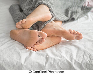 Close-up of the feet of a couple on the bed.