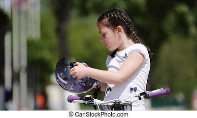 Close-up of the girl wearing helmet and then rides a bicycle in the city park.