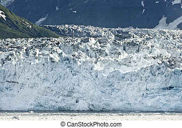 Close up of the glacier's edge reaching the ocean in alaska.