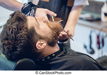 Close-up of the hand of a barber trimming the beard of a customer