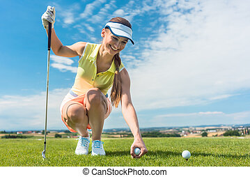 Close-up of the hand of a female player holding a ball above the golf course