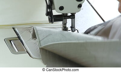 Closeup of seamstress machine-sewing a white shirt