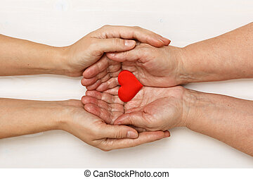 Close-up of the hand of an adult daughter and an older mother holding a heart together. Top view. Family and care concept