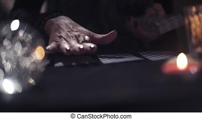 Close-up of the hand of an unknown witch woman is moves above the cards on the table in magic salon with dark light and blury candles. Concept of storytelling and magic spells