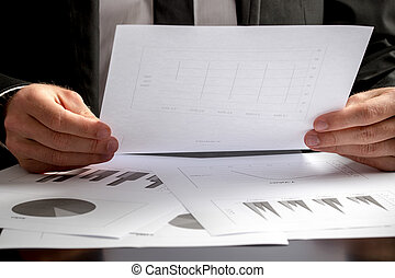 Close up of the hands of a businessman analysing a set of graphs
