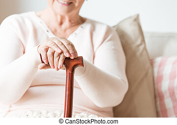 Close-up of the hands of a happy, elderly woman resting on a wooden cane