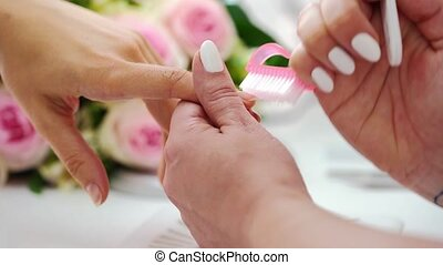 Close-up of the hands of a qualified manicurist filing the nails of a young woman in beauty parlor