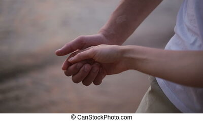 Close-up of the hands of a young couple gently pat each other on the beach