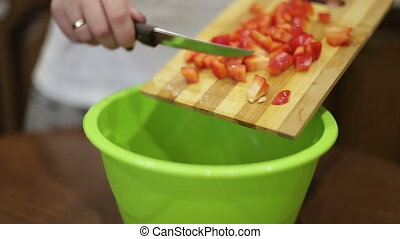 Close-up of the hands of a young woman lays down the fruits of a wooden board in a green bowl