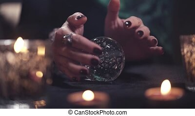 Close-up of the hands of an unidentified female magician drifted over a glass ball during a divination session. Concept of magic and recognition of future events in life