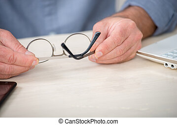 close up of the hands of senior man with glasses