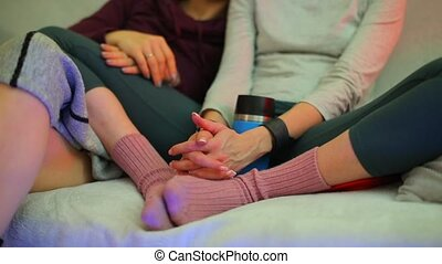 Close-up of the hands of two girls sitting and talking on the couch.