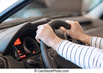 Close up of the hands on steering wheel