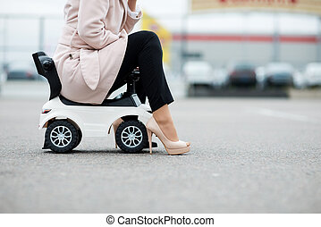 close-up of the legs of a woman sitting on a baby car that is standing on the pavement