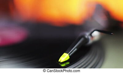 close-up of the needle of dj record player, with abstract coloured lights in background