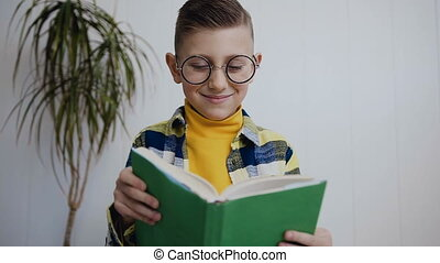 Close- up of the nice little schoolboy in glasses who read a book while sitting on the floor at home near white wall. Indoors. Portrait