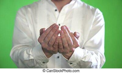 Close-up of the palm of a man in a shirt on a green background