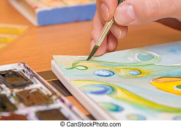 Close-up of the process of drawing watercolor on paper
