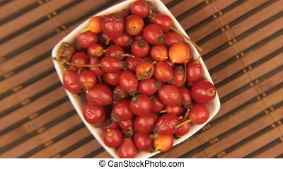 Close-up of the rotation of a dish with rosehips through a...