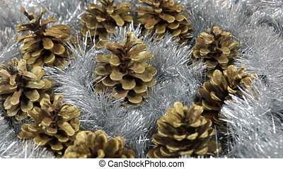 Close-up of the rotation of silver tinsel and golden pine...