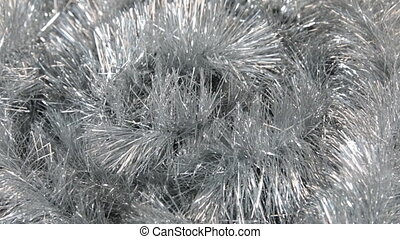 Close-up of the rotation of silver tinsel under the wind....