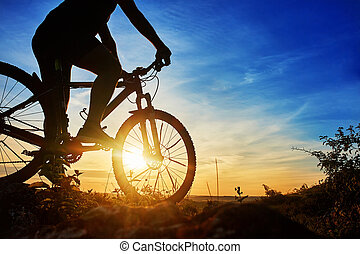 Close-up of the silhouette of young man cyclist on sunset sky with clouds.