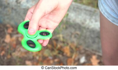 Close up of the spinner in teen's hand. Girl holding spinner