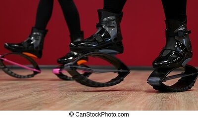 Close-up of the sport girl holding kangoo jumps. Girls are...