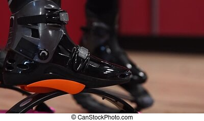Close-up of the sport girl holding kangoo jumps. Girls are ...