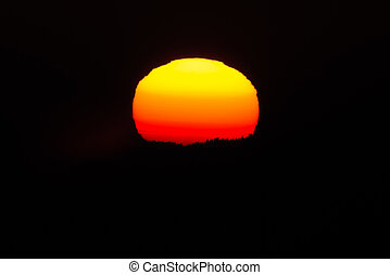 Close up of the sun during sunset at a cold winter night