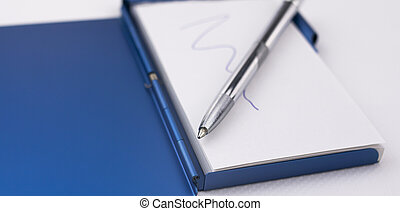 Close-up of the tip of a silver pen on a notepad to write down reminders