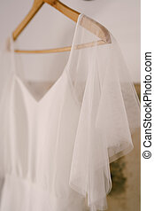 Close-up of the top of the bride's dress on a wooden hanger.