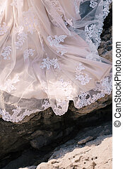Close-up of the train of a bride dress on a stone texture.