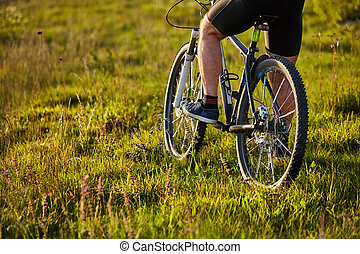 Close-up of the wheel of a bicycle and legs of the cyclist on the meadow.