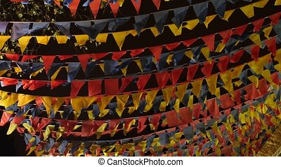 close-up of the wind flaps of a garland of colorful flags against the background of the night sky. Copy space 4K