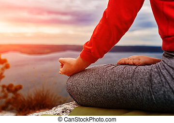 Close-up of the woman sitting in lotus position and meditating on the rock.