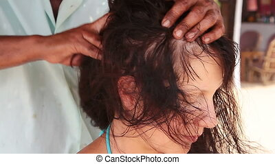 Close up of therapist's hands doing head massage on woman.