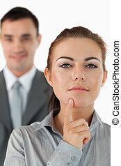 Close up of thinking businesswoman with colleague in the background against a white background