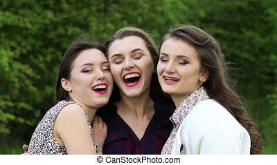 Close up of three girls in embrace smiling and looking at a camera. Slowly