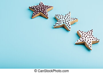 Close-up of three homemade glazed gingerbread cookies made in the form of stars on a blue background. Handmade cookies. Free space.