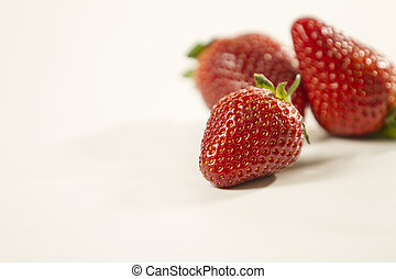 Close-up of three strawberries isolated on white background shot in high angle view with selective focus