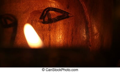 Close up of totem face lit by candle
