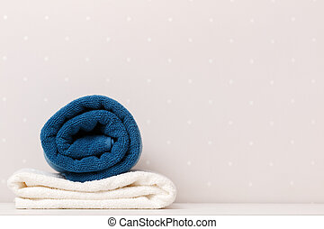 Close-up of towels blue and white color lay on a table against the background of light walls