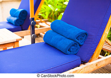 Close-up of towels near swimming pool at tropical resort