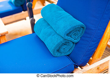Close-up of towels on the loungers near swimming pool